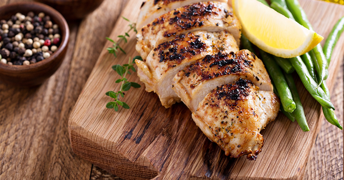 Grilled chicken on a cutting board with thyme and green beans; blog: heart healthy food swaps