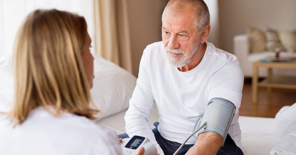 Health visitor and a senior man during home visit. A nurse checking blood pressure of a man; blog: 10 Effects of High Blood Pressure
