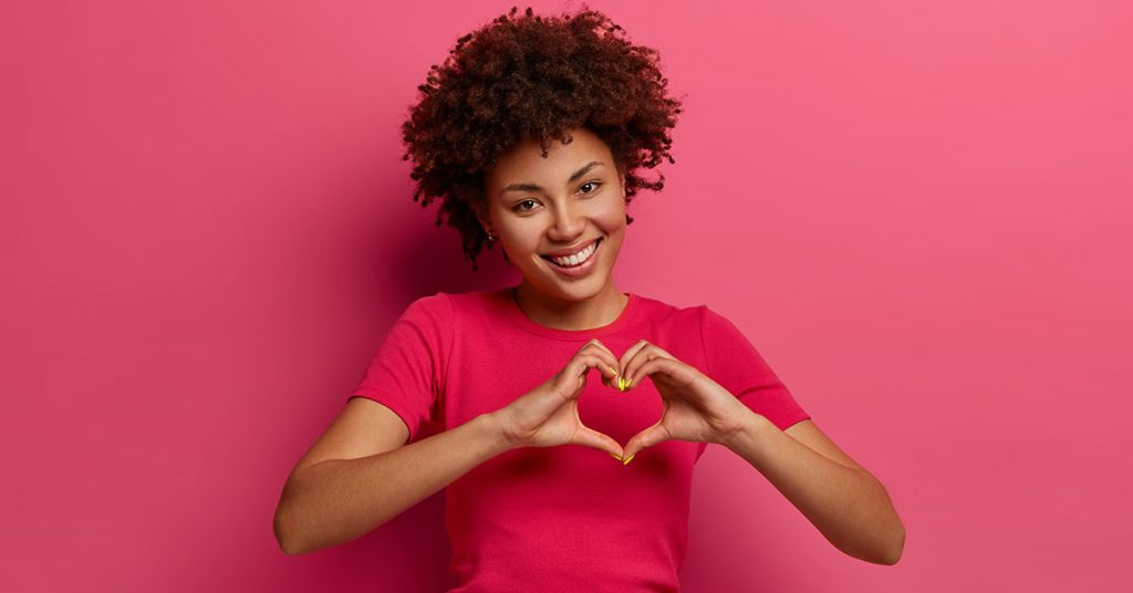 Pretty curly African American woman confesses in love, makes heart gesture, shows her true feelings, has happy expression, wears casual red t shirt, poses over pink background. Relationship concept; blog: 7 Ways to Be Heart Healthy At Home