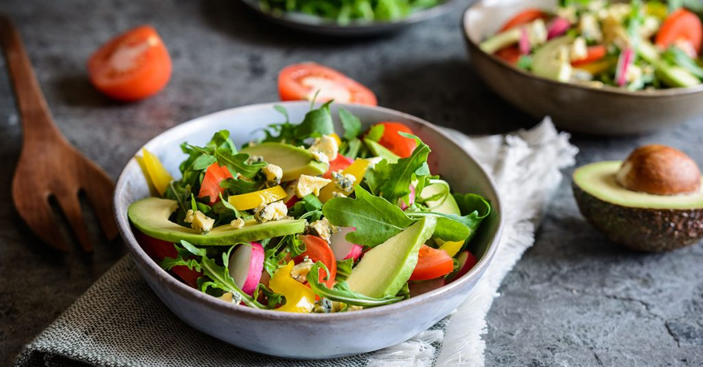 Healthy raw arugula salad with avocado, radish, bell pepper, tomato and Roquefort cheese; blog: 5 Summer Foods for Heart Health