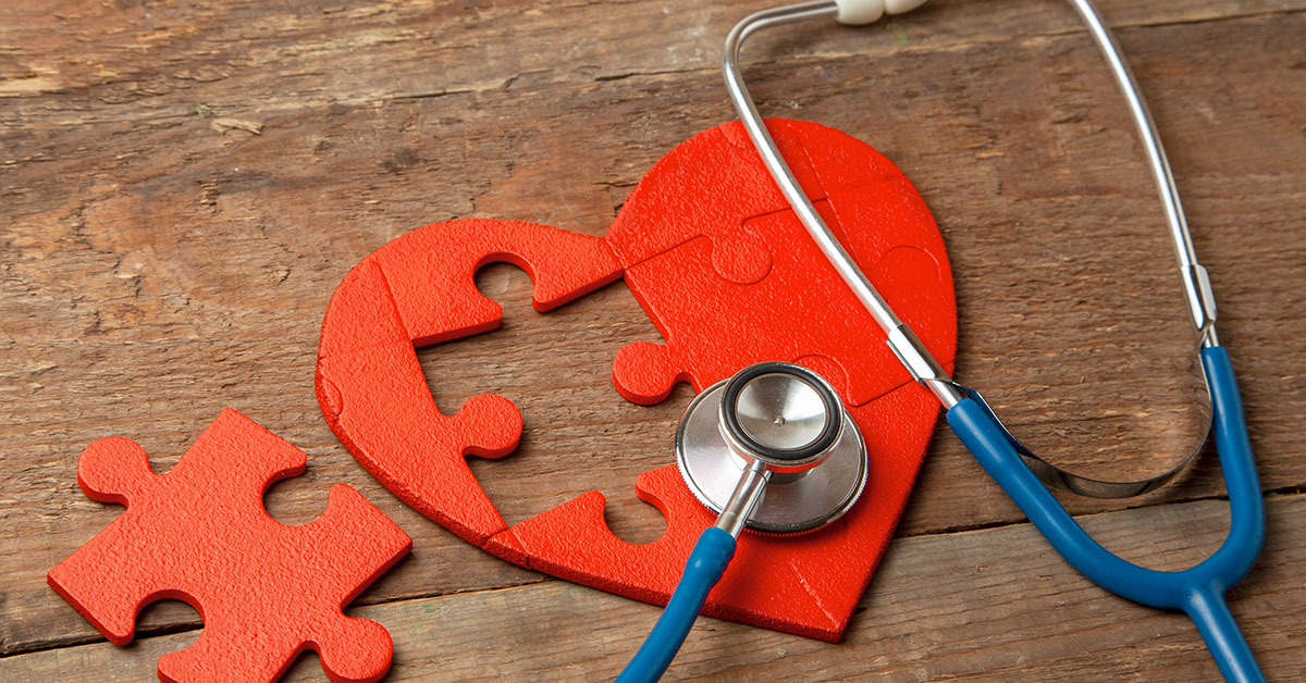 Heart puzzle red and stethoscope on wooden background. Concept diagnosis and treatment of heart disease, medical insurance; blog: What is Structural Heart Disease?
